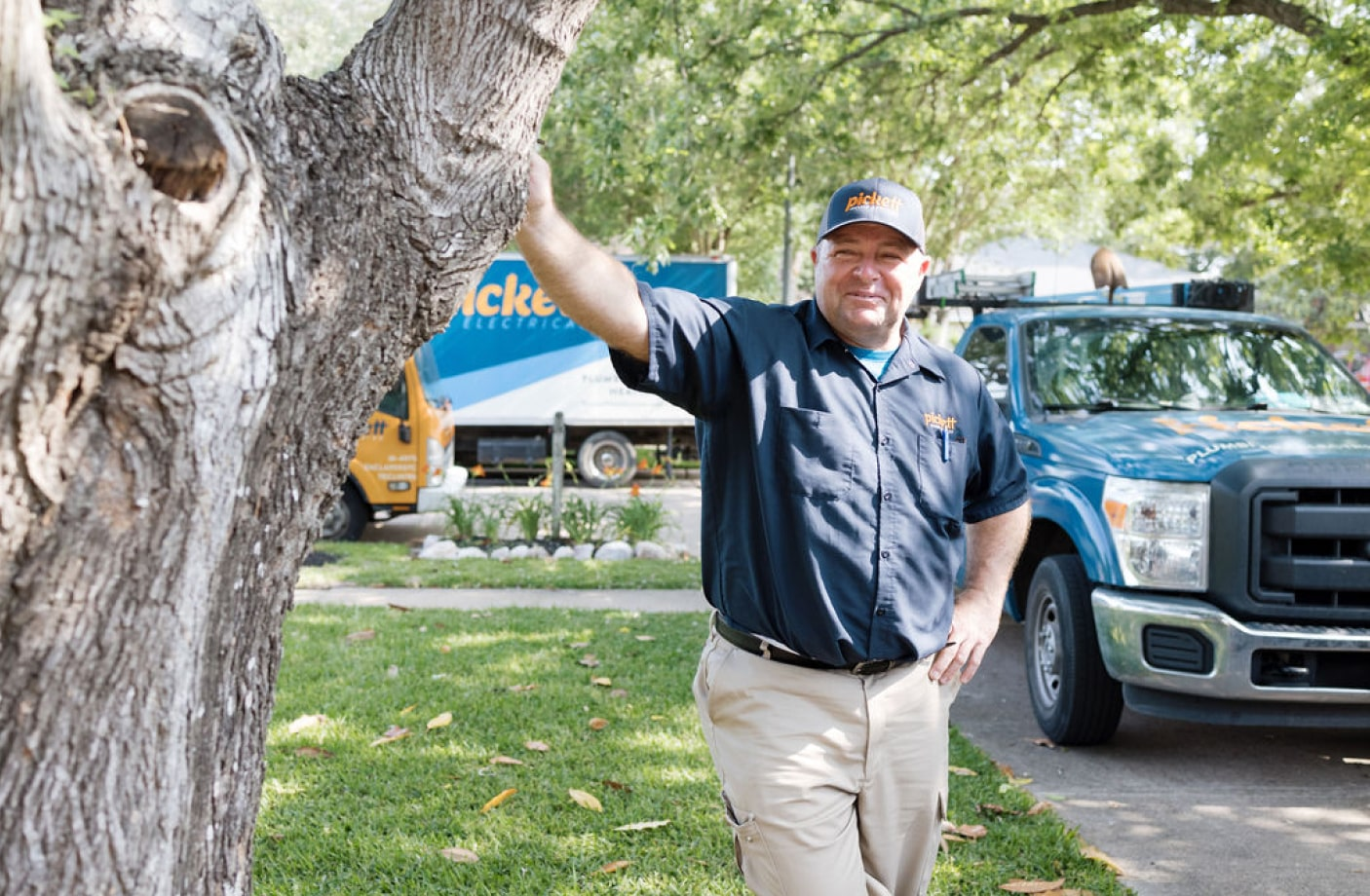 plumber smiling leaning on a tree