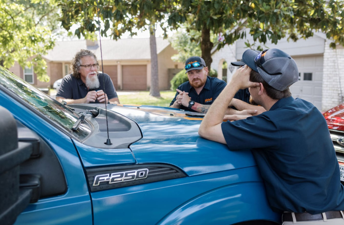 plumbers leaning on truck talking with customer