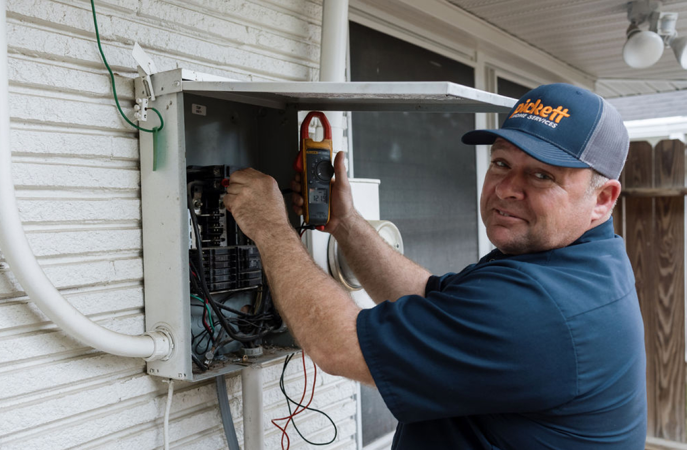 man smiling while working on breaker box